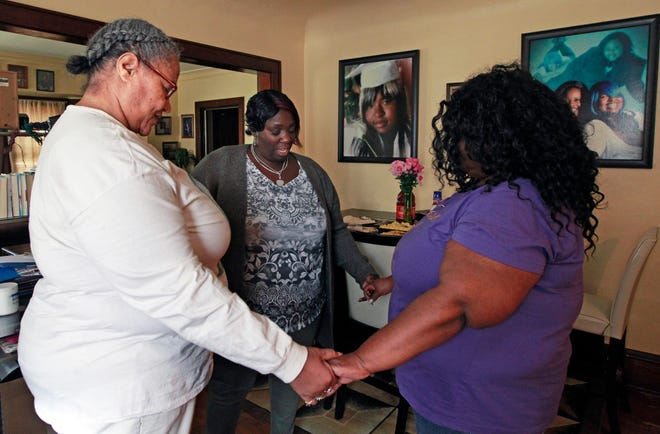 Tanja Dixon, from left, Shannon Allen  and Gloria Nichols pray before brunch at Nichols' home. The three mothers lost sons to homicide and met in a grief support group.