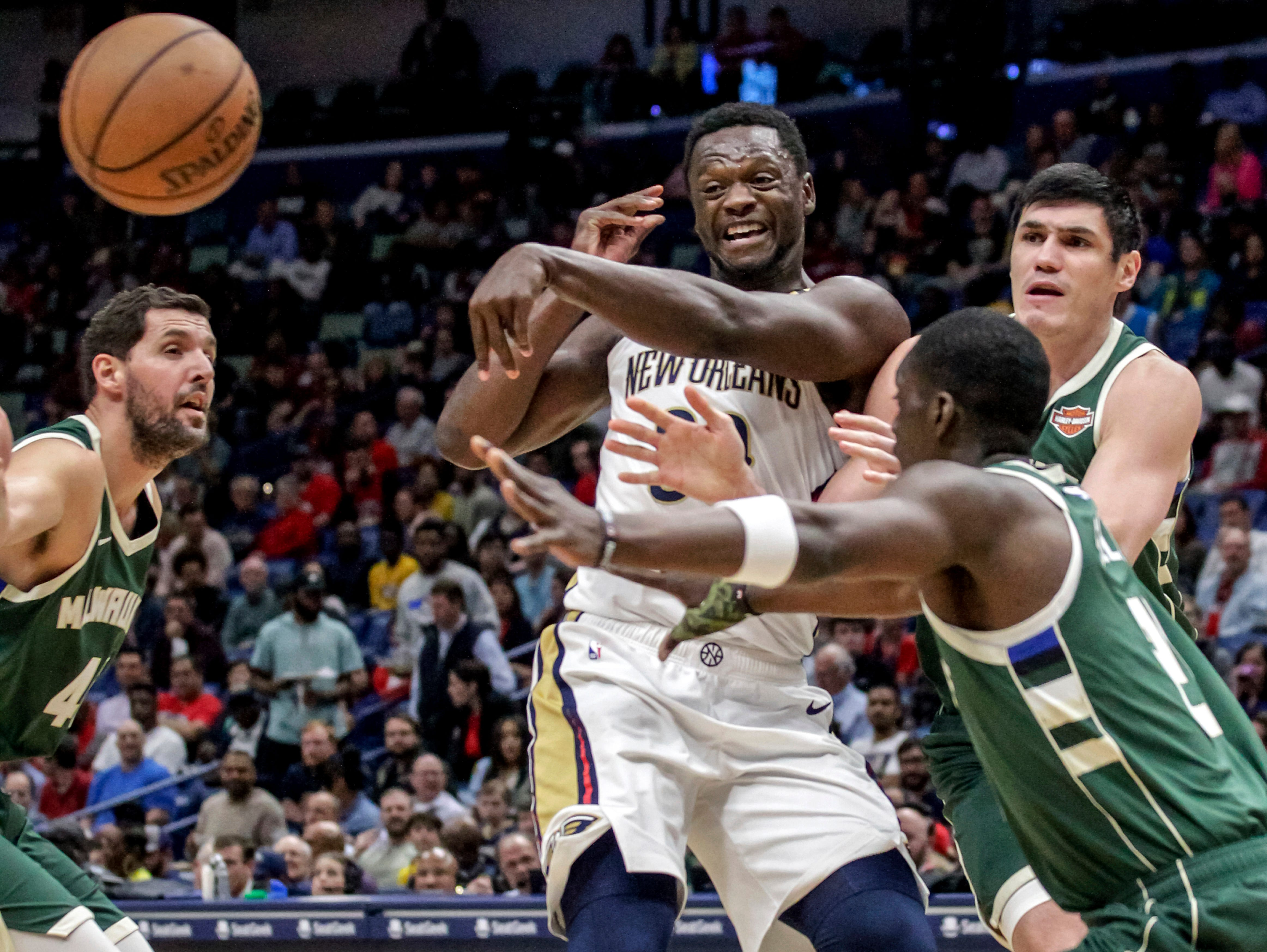 Pelicans center Julius Randle is forced to give up the rock as he's surrounded by Nikola Mirotic (left), Tony Snell (center) and Ersan Ilyasova during the first half Tuesday.