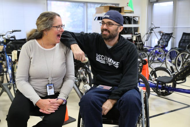 Joyce Casey, a recreational therapist at the Zablocki Veterans Affairs Medical Center in Milwaukee, jokes with Noah Currier of Poplar Grove, Illinois. Currier, a quadriplegic, who gets care at the VA's Spinal Cord Injury Center. Currier started Oscar Mike clothing company, with profits going to a foundation supporting injured veterans.