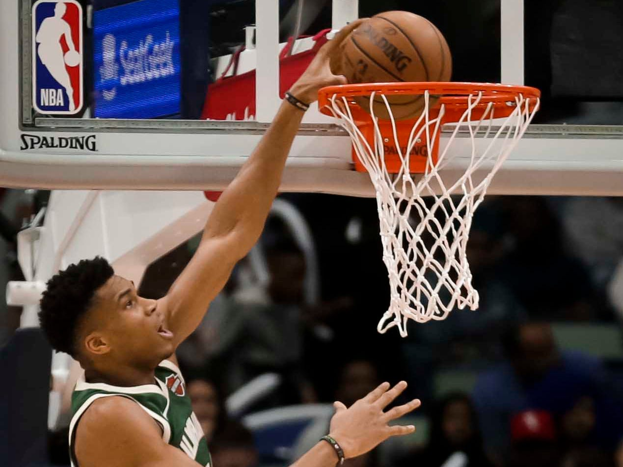 Bucks forward Giannis Antetokounmpo throws down a dunk during the second quarter as Pelicans forward Solomon Hill looks on.