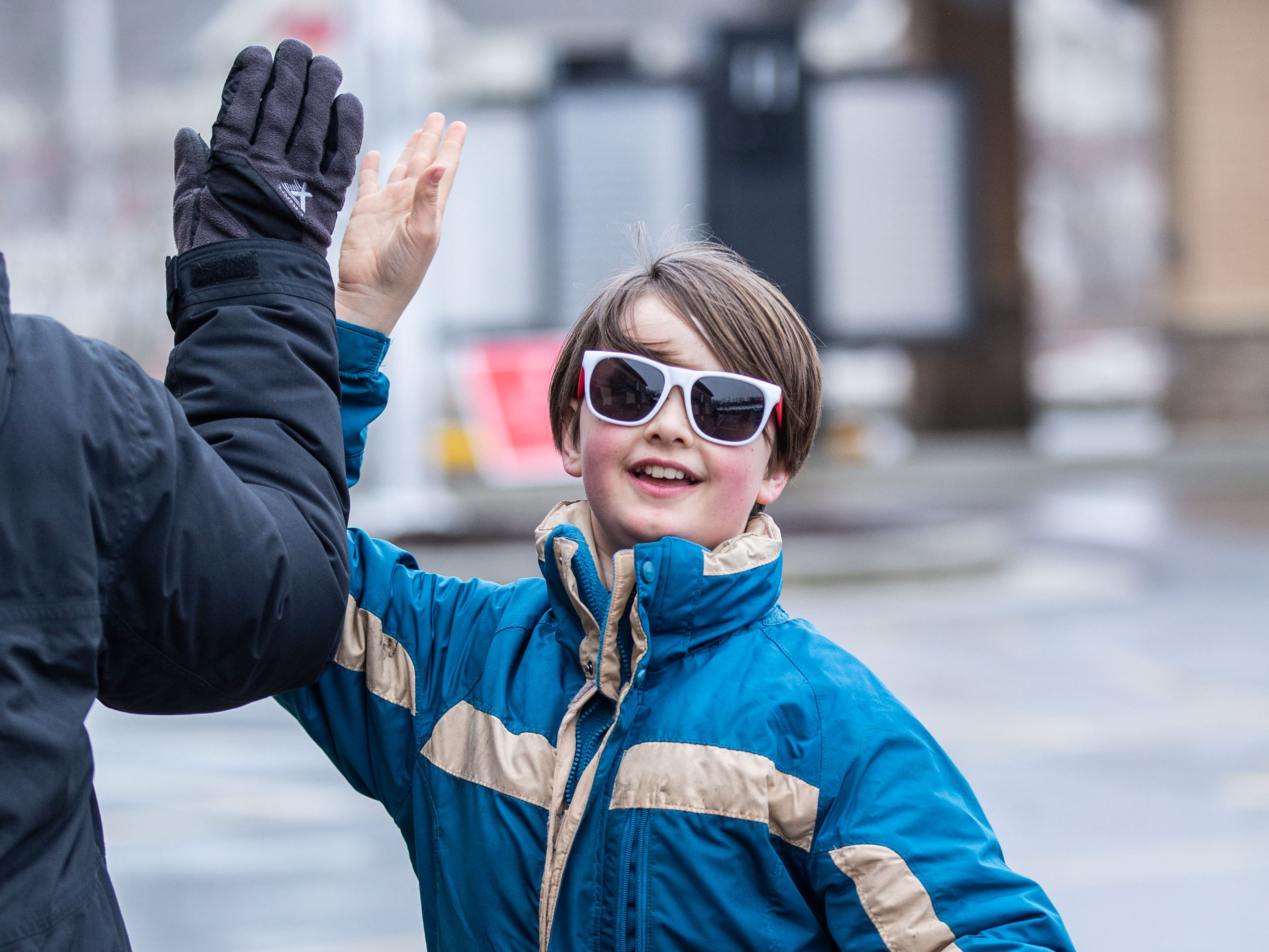 Gabe Borkenhagen, 11, of Waukesha gets a high five after winning a pair of sun glasses outside Pewaukee's new Chick-fil-A location at 1454 Capitol Drive on Wednesday, March 13, ahead of Thursday's grand opening. Chick-fil-A is holding The First 100 Camp Out contest which offers a year's worth of free Chick-fil-A to the first 100 participants.