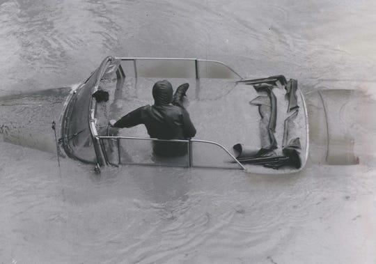 A skin diver sits in a submerged convertible in Wauwatosa on West Capitol Drive just west of Highway 100 on March 30, 1960. The diver had hitched a tow line to the vehicle and was waiting for it to be pulled out. This photo was published in the March 31, 1960, Milwaukee Journal.