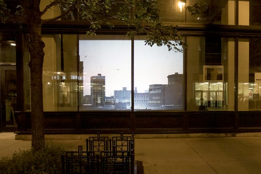 A projection is seen in a vacant storefront on Wisconsin Avenue next to Mo's Irish Pub. Photographer Dick Blau provided the bench for viewers who want to sit a while.
