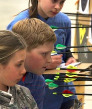Participants score shots at the Wisconsin Indoor Championships of the Scholastic 3-D Archery (S3DA) program.