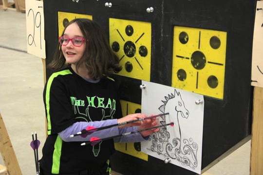 "Brittany Lewin of Algoma retrieves her arrows during a special ""Dragon Shoot"" following her session."