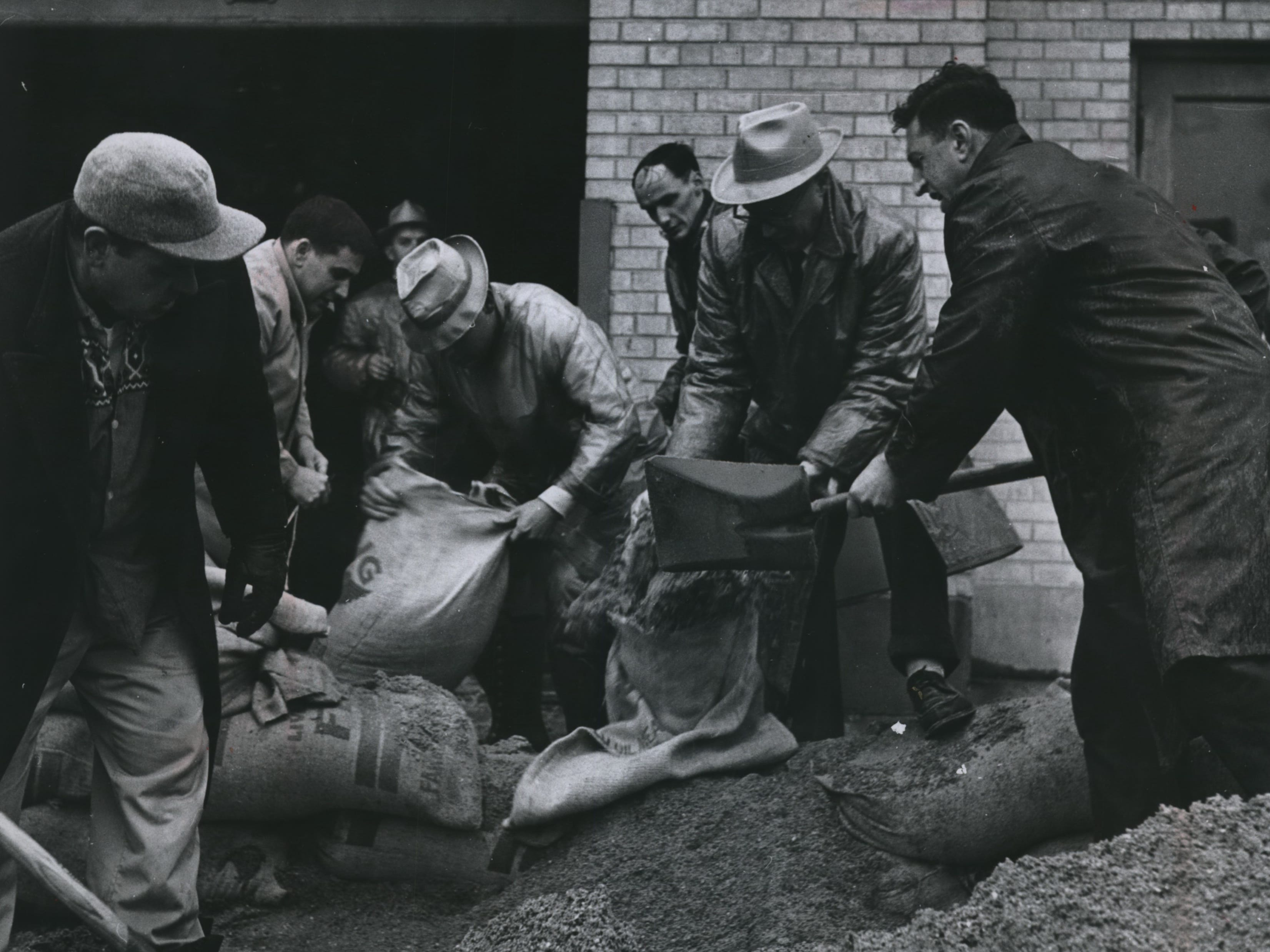 Employees of the Sears, Roebuck & Co. store on South Barstow Street in downtown Waukesha make a sandbag barricade to protect the store from the overflowing Fox River on March 30, 1960. This photo was published in the Milwaukee Journal on March 31, 1960.