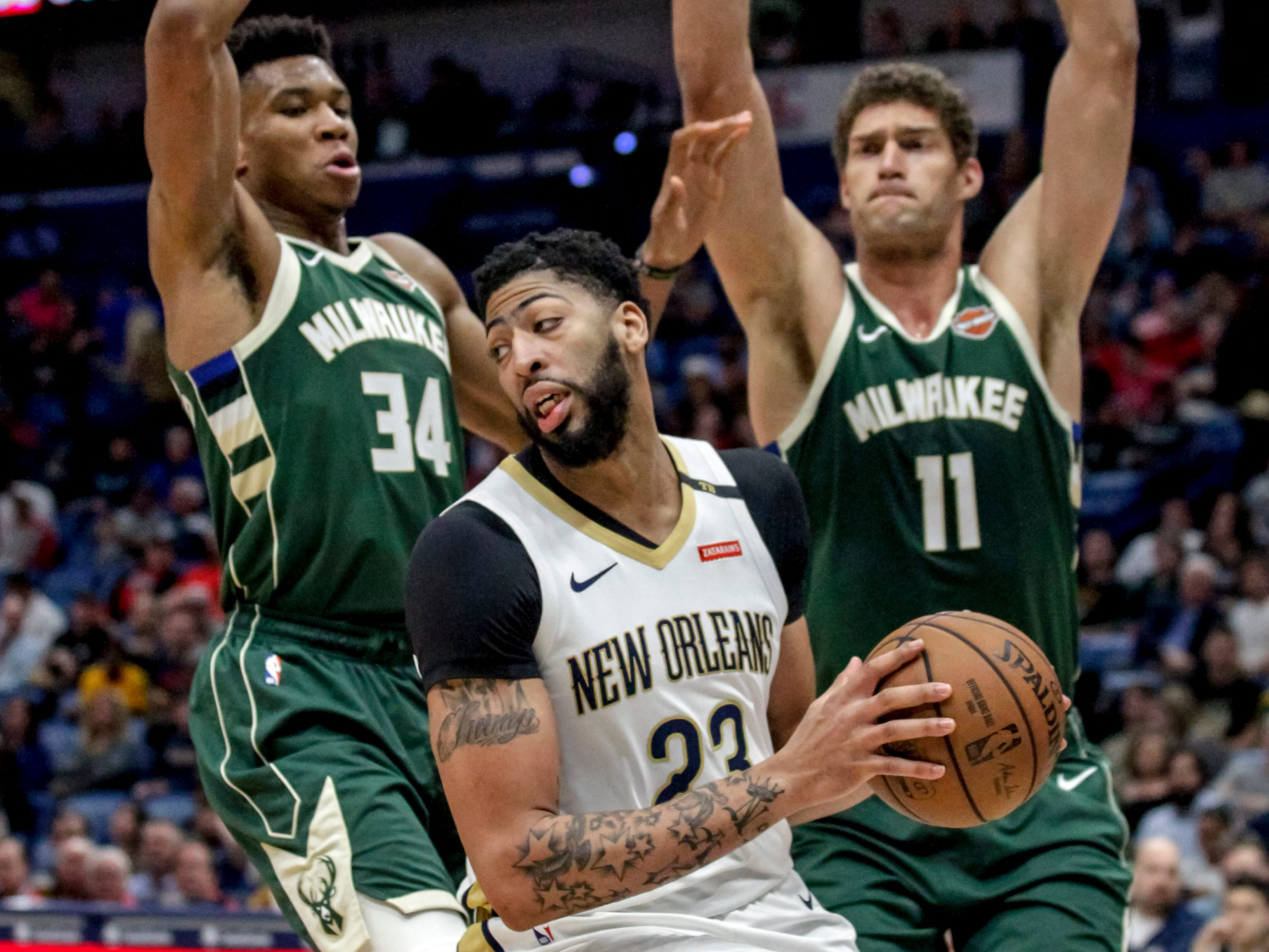 Pelicans forward Anthony Davis gets pinned along the baseline by Giannis Antetokounmpo and Brook Lopez of the Bucks during the first half.
