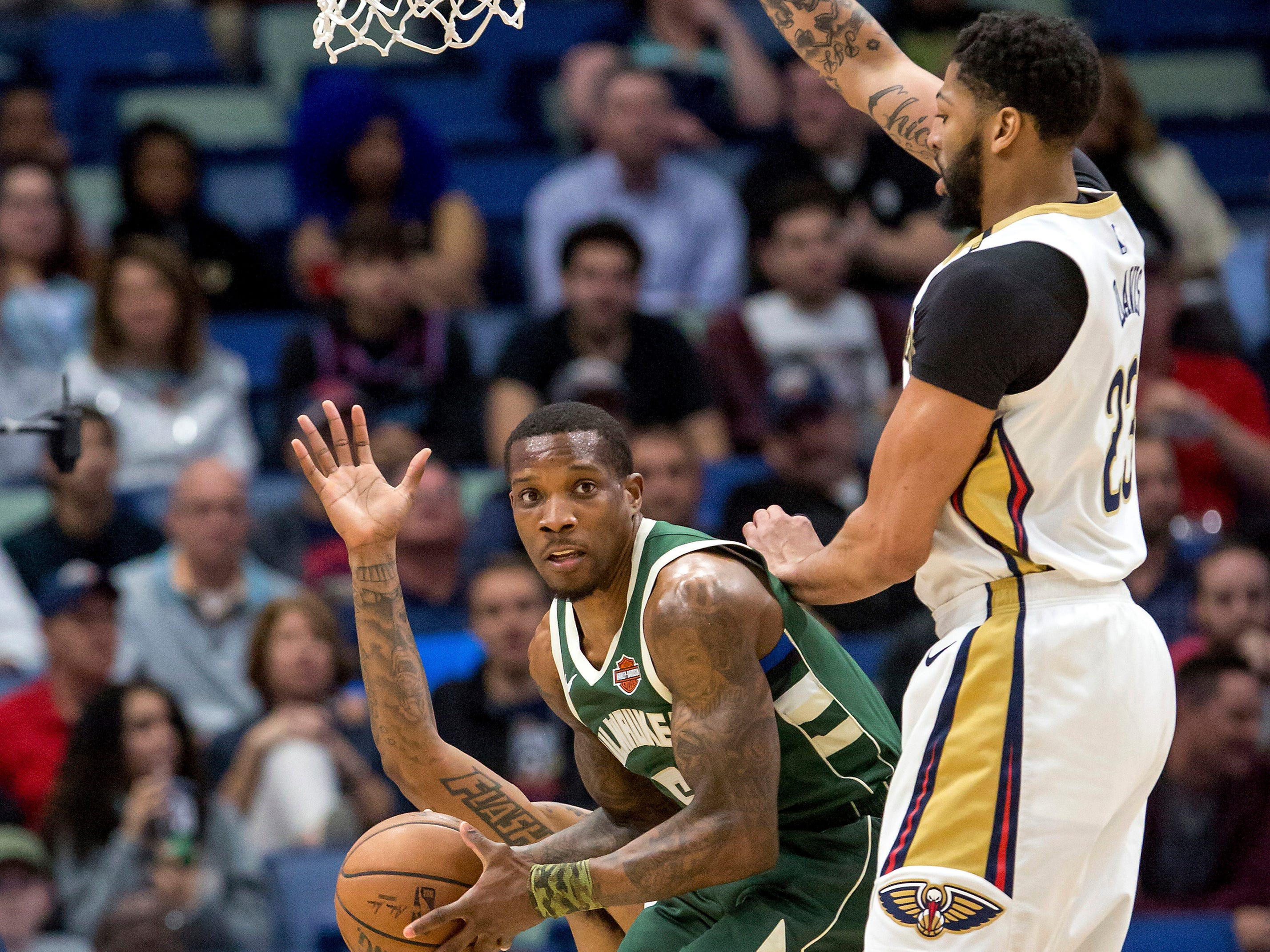 Bucks guard Eric Bledsoe is forced to kick a pass out to a team after being met by Pelicans forward Anthony Davis on a drive to the basket during the first half.