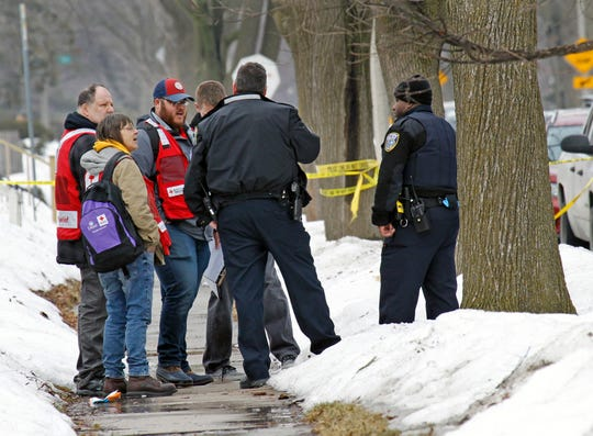 Representatives from the American Red Cross talk with first responders at the scene of a house fire near North 39th Street and West Silver Spring Drive on Wednesday that claimed the lives of two people.