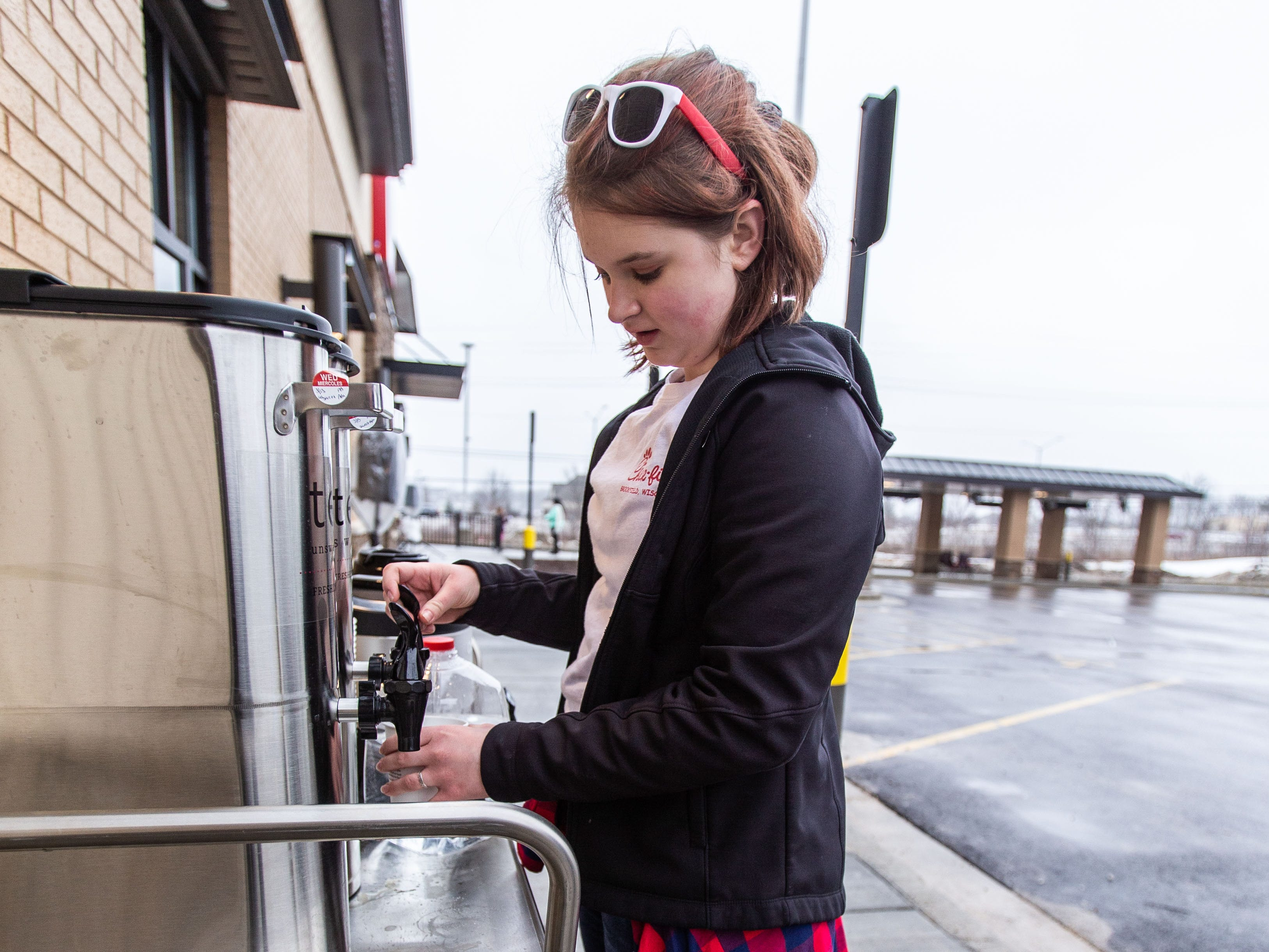 Allie Borkenhagen, 15, of Waukesha fills a cup of tea outside Pewaukee's new Chick-fil-A location at 1454 Capitol Drive on Wednesday, March 13, ahead of Thursday's grand opening. Chick-fil-A is holding The First 100 Camp Out contest which offers a year's worth of free Chick-fil-A to the first 100 participants.