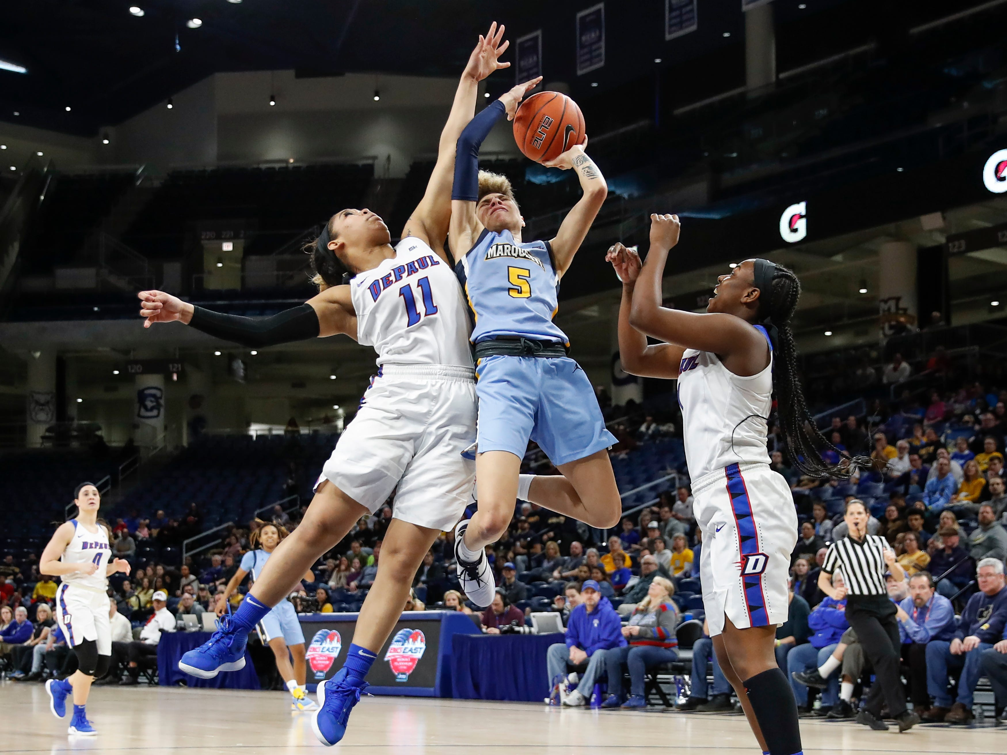 Marquette guard Natisha Hiedeman puts up a shot as she's fouled by DePaul guard Sonya Morris (11)during the first half.