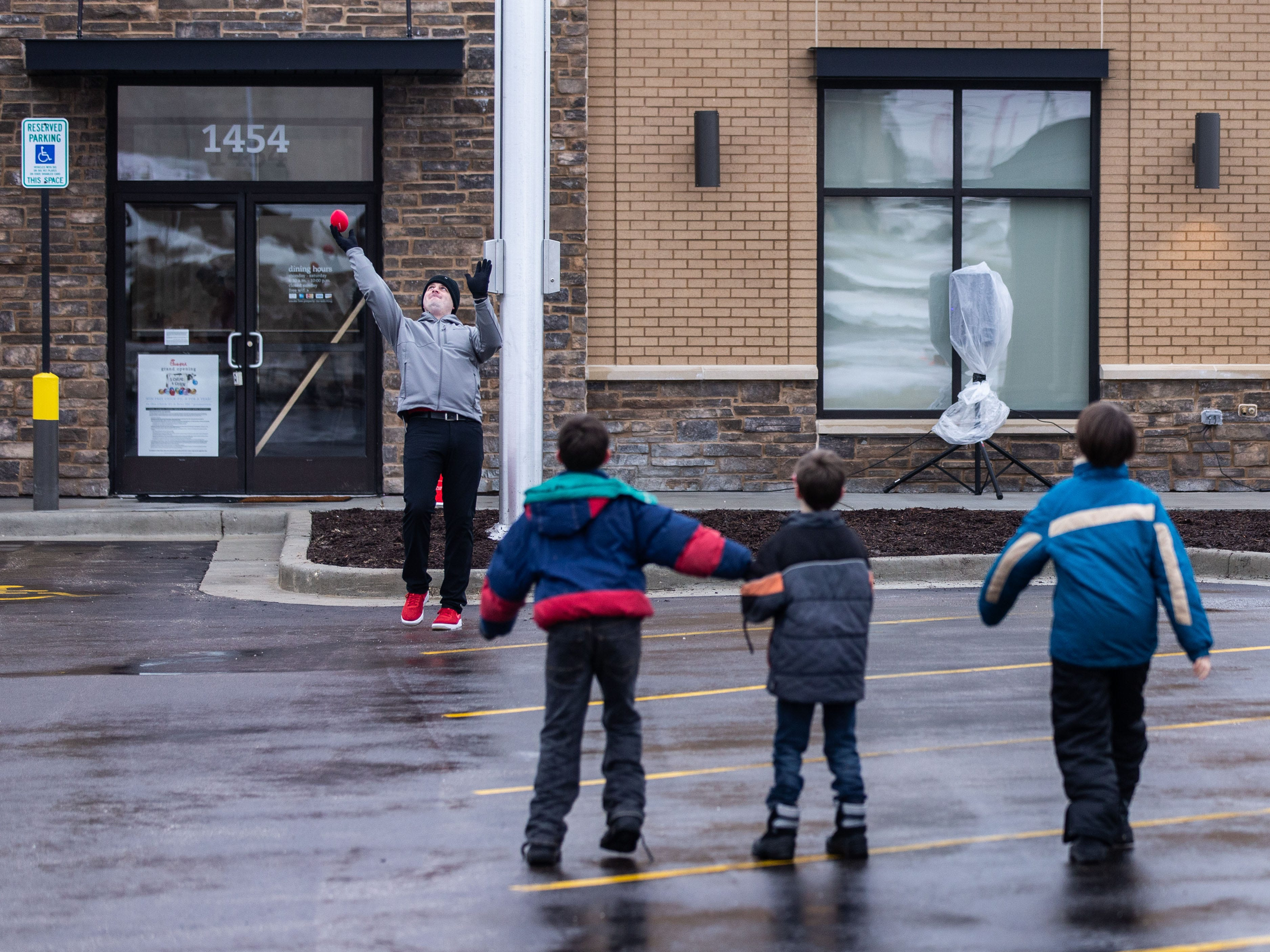 Chick-fil-A employee Matt Peele plays football with campers outside Pewaukee's new Chick-fil-A location at 1454 Capitol Drive on Wednesday, March 13, ahead of Thursday's grand opening. Chick-fil-A is holding The First 100 Camp Out contest which offers a year's worth of free Chick-fil-A to the first 100 participants.