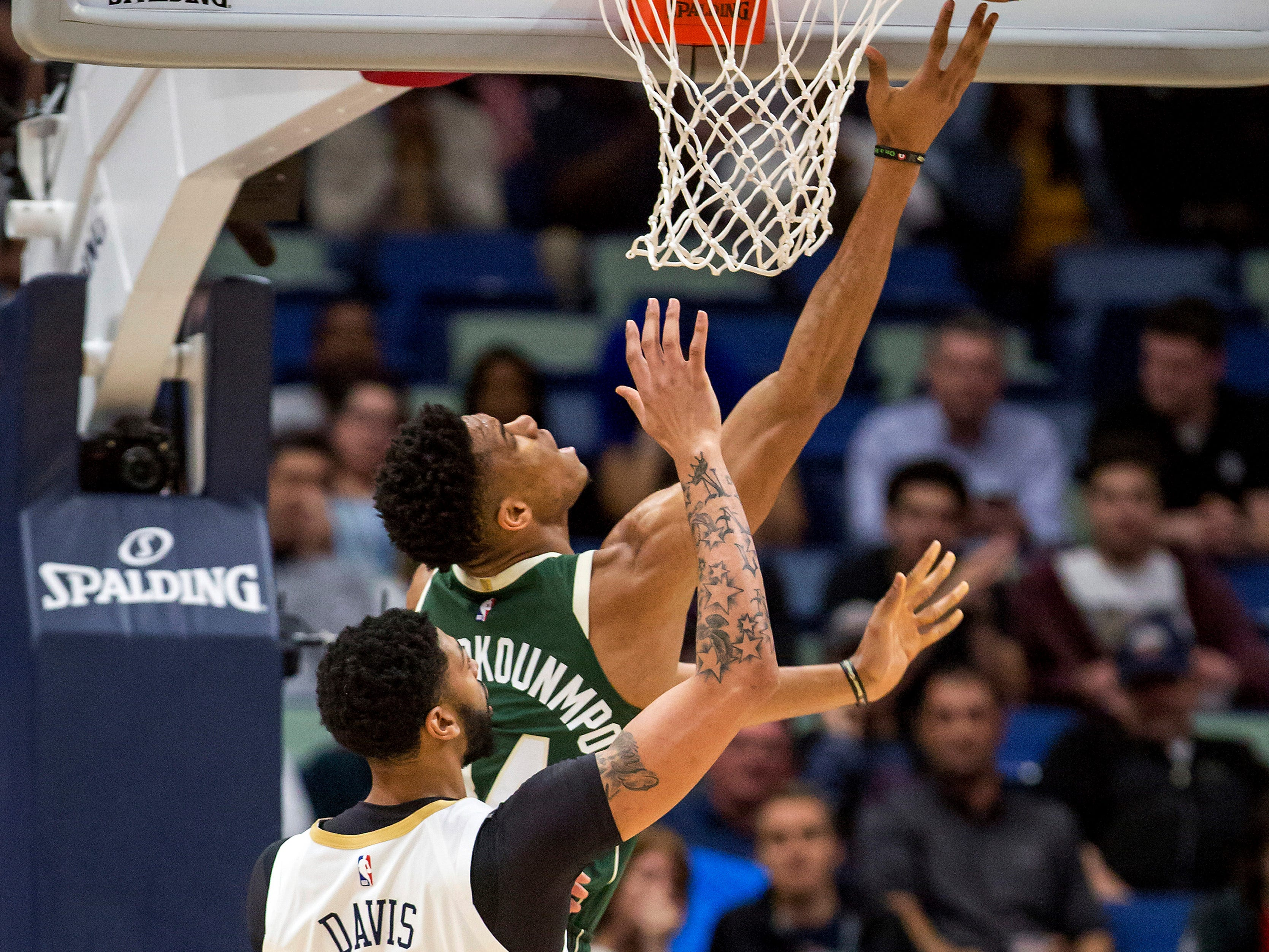 Bucks forward Giannis Antetokounmpo is fouled by Pelicans forward Anthony Davis during the first half.