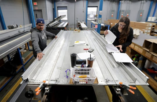 DJ Mireles (left) works on custom corner guards and Dana Thomas checks custom orders March 13 in the vinyl fabrication area at Inpro Corp. in Muskego.