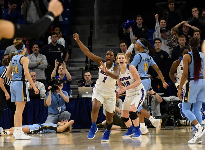 Marquette players are left stunned and dejected as Ashton Millender (1) and Lexi Held start celebrating DePaul's 74-73 victory over the Golden Eagles in the championship game of the Big East Tournament on Tuesday night in Chicago.