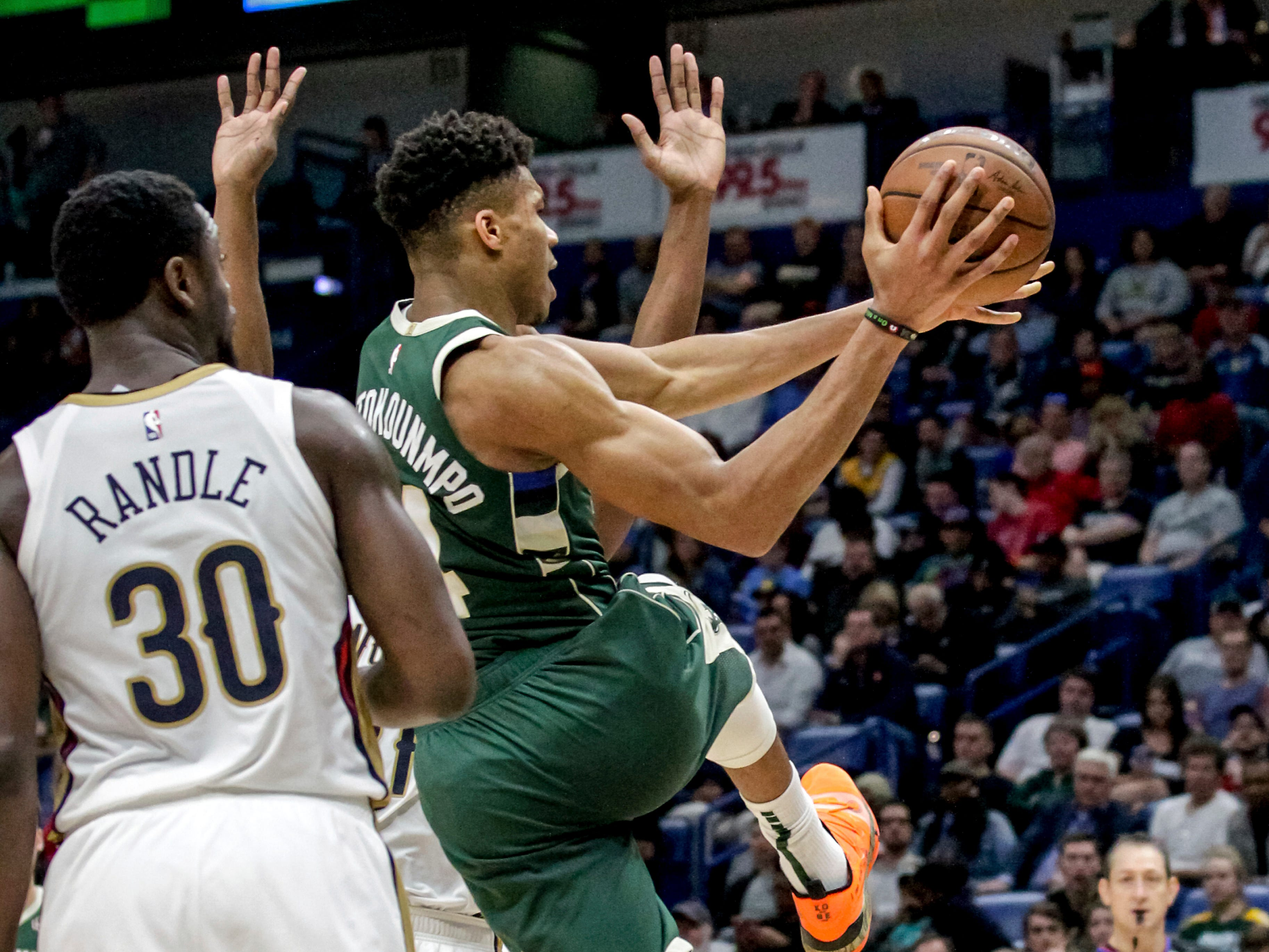 Bucks forward Giannis Antetokounmpo kicks a pass out to a teammate while being guarded by Pelicans center Julius Randle in the second half.