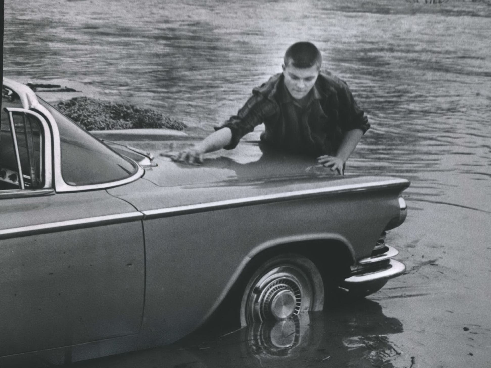 Nick Mollgaard of Wauwatosa cleans off his car as it stands in nearly a foot of water west of downtown Wauwatosa, where the Menomonee River had overflowed their banks. This photo was published in the March 30, 1960, Milwaukee Journal.