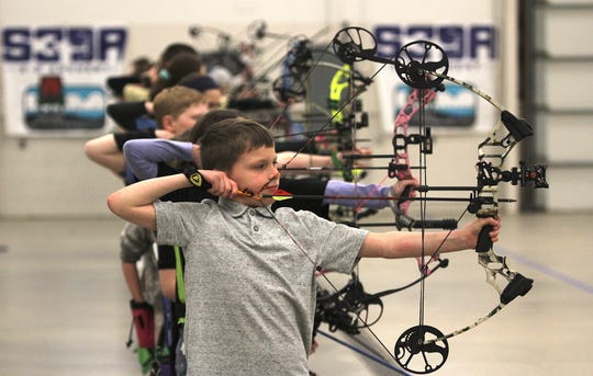 Trace Duchateau, a fourth-grader from Richfield, takes aim along with a flight of 30 archers at the Wisconsin State Indoor Championships of the Scholastic 3-D Archery program.