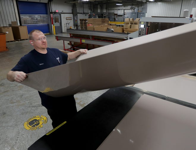 Darius Kowalik removes a newly created  8-foot sheet of PVC in the extrusion department at Inpro Corp. in Muskego.