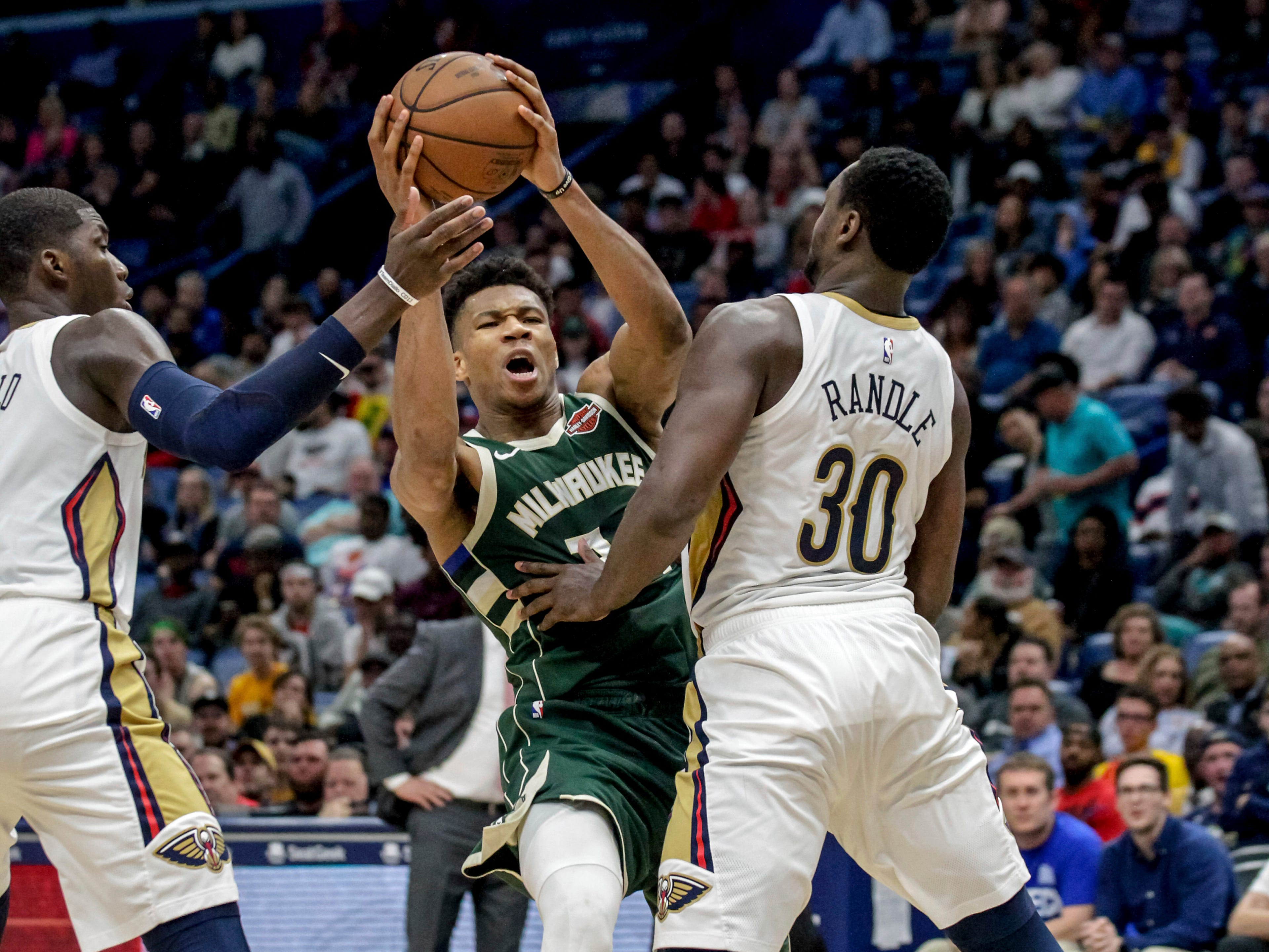 Bucks forward Giannis Antetokounmpo attempts to get between Julius Randle (30) and Cheick Diallo of the Pelicans during a drive in the second half.
