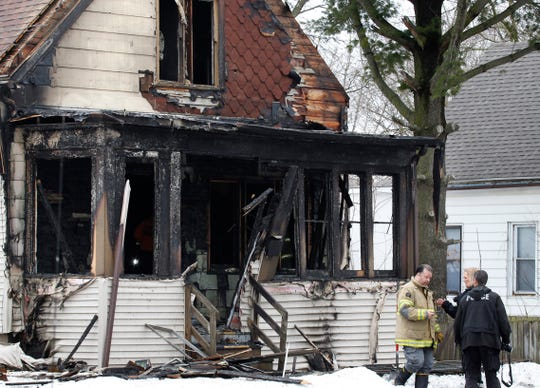 Investigators talk at the scene of a house fire near North 39th Street and West Silver Spring Drive on Wednesday that claimed the lives of two people.