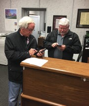 Norfork high school principal Bobby Hulse (left) and history teacher Kevin Bodenhamer text out the voting results of the district's proposed millage increase Tuesday night at the Baxter County Courthouse.