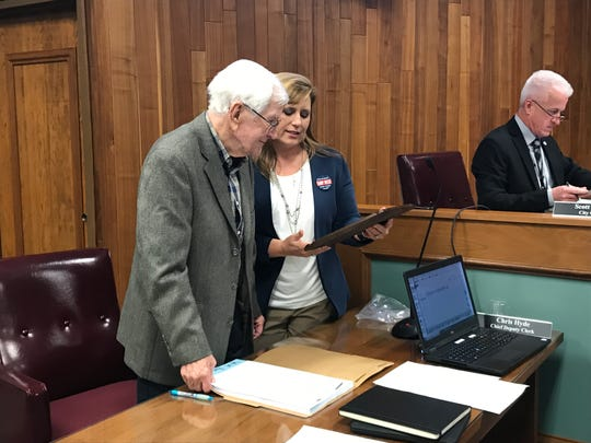 "West Monroe Mayor Staci Mitchell reads a plaque for retiring alderman James ""Sonny"" Bennett, who has served on the board of aldermen for 45 years and is leaving due to health complications."