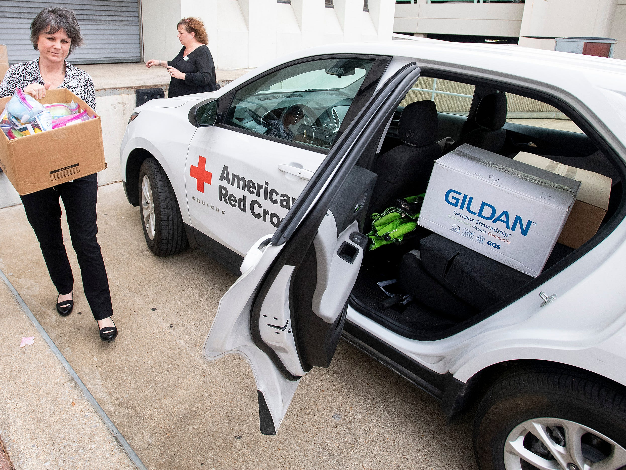 Dallas Rabig, of the Department of Early Childhood Education, left, gives child comfort kits to Kelly Hodges, of the Red Cross, on Wednesday March 13, 2019 in Montgomery, Ala., to be distributed to children in the wake of the Lee County tornados.