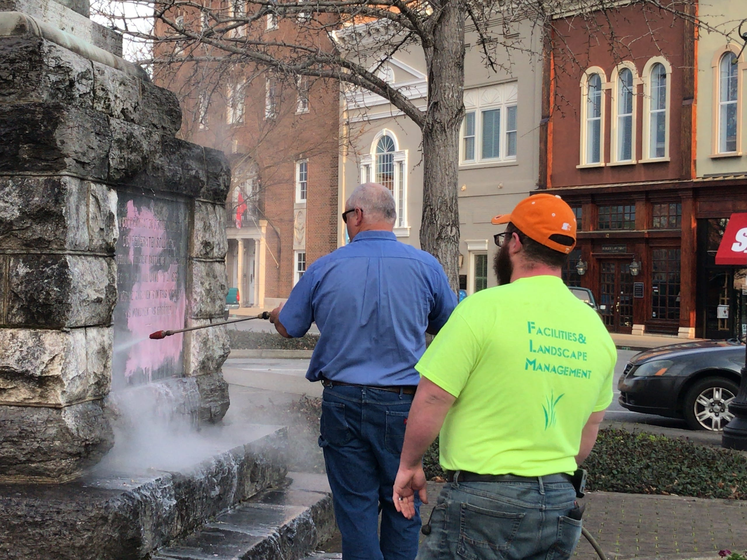 Two men clean the Confederate statue on  the Murfreesboro square that was vandalized overnight on Tuesday, March 12, 2019.