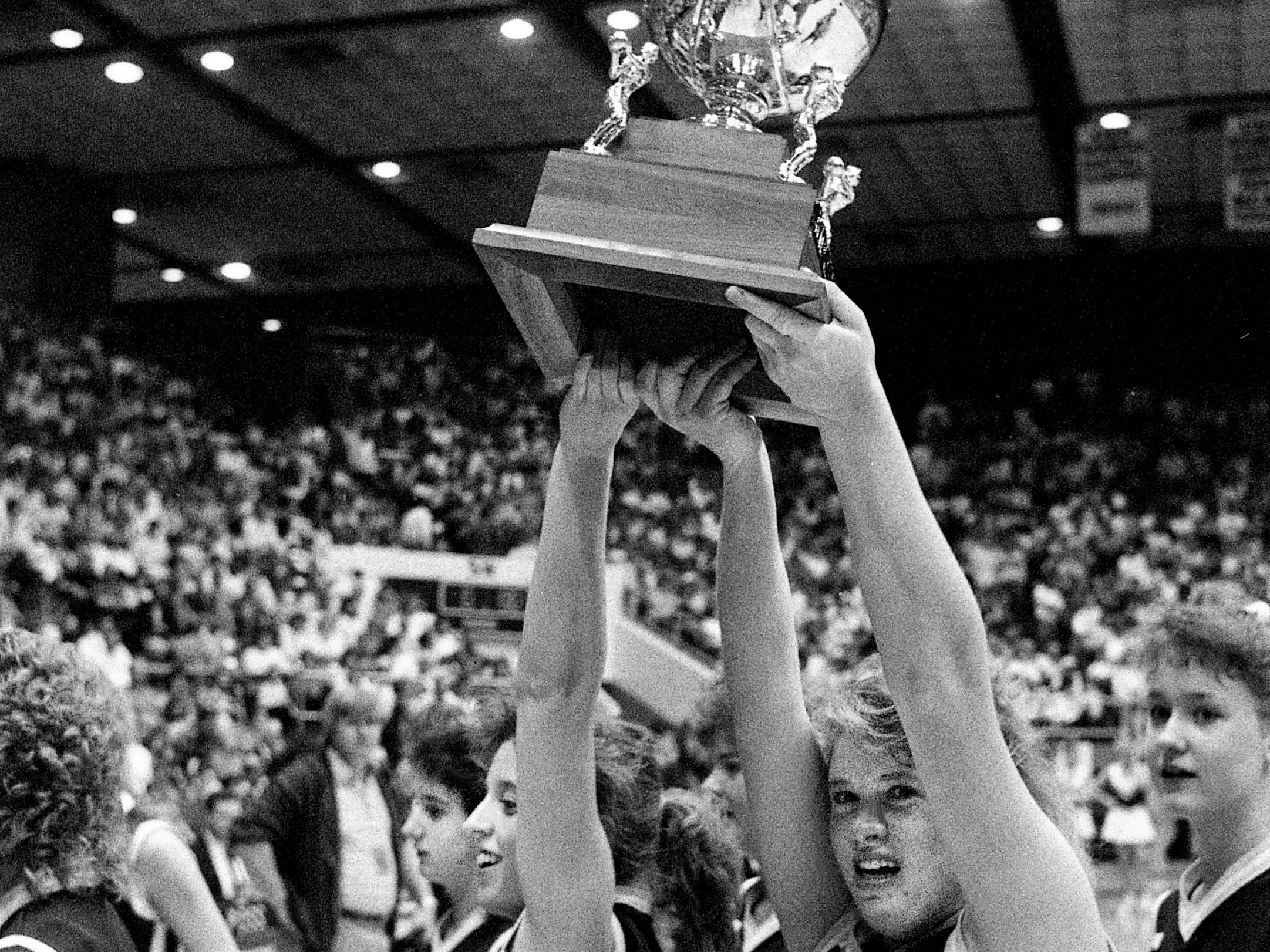 Cannon County High's Tracey Smithson, left, and Reggie King (50) hoist the Class AA title trophy after defeating Happy Valley High 51-46 in the TSSAA State Tournament at MTSU's Murphy Center in Murfreesboro on March 11, 1989. Cannon County had lost in the finals the past two years to South Greene High.