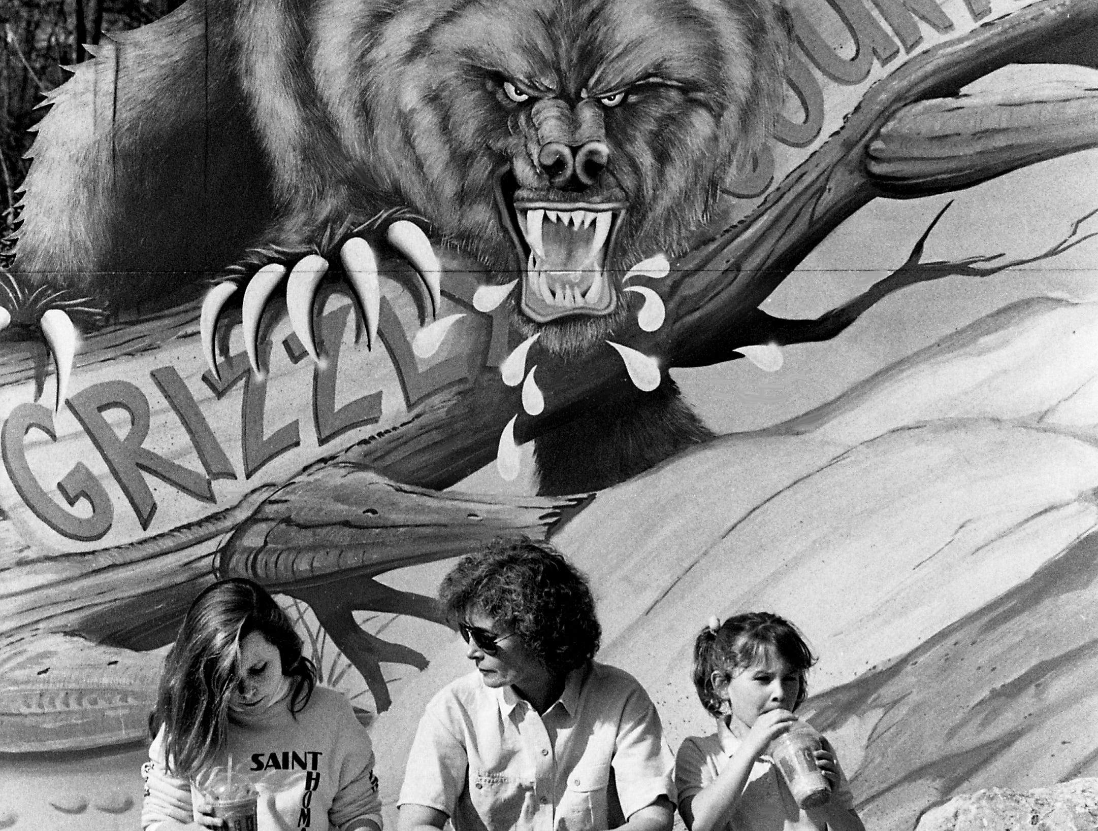 Stephanie Nadeau, center, and daughters Jessica, 12, left, and Kate, 6, of Nashville, enjoy a break during their visit to opening day of the 18th season of the Opryland U.S.A. theme park on March 25, 1989, while the painted grizzly behind them looks like he wants a snack also.