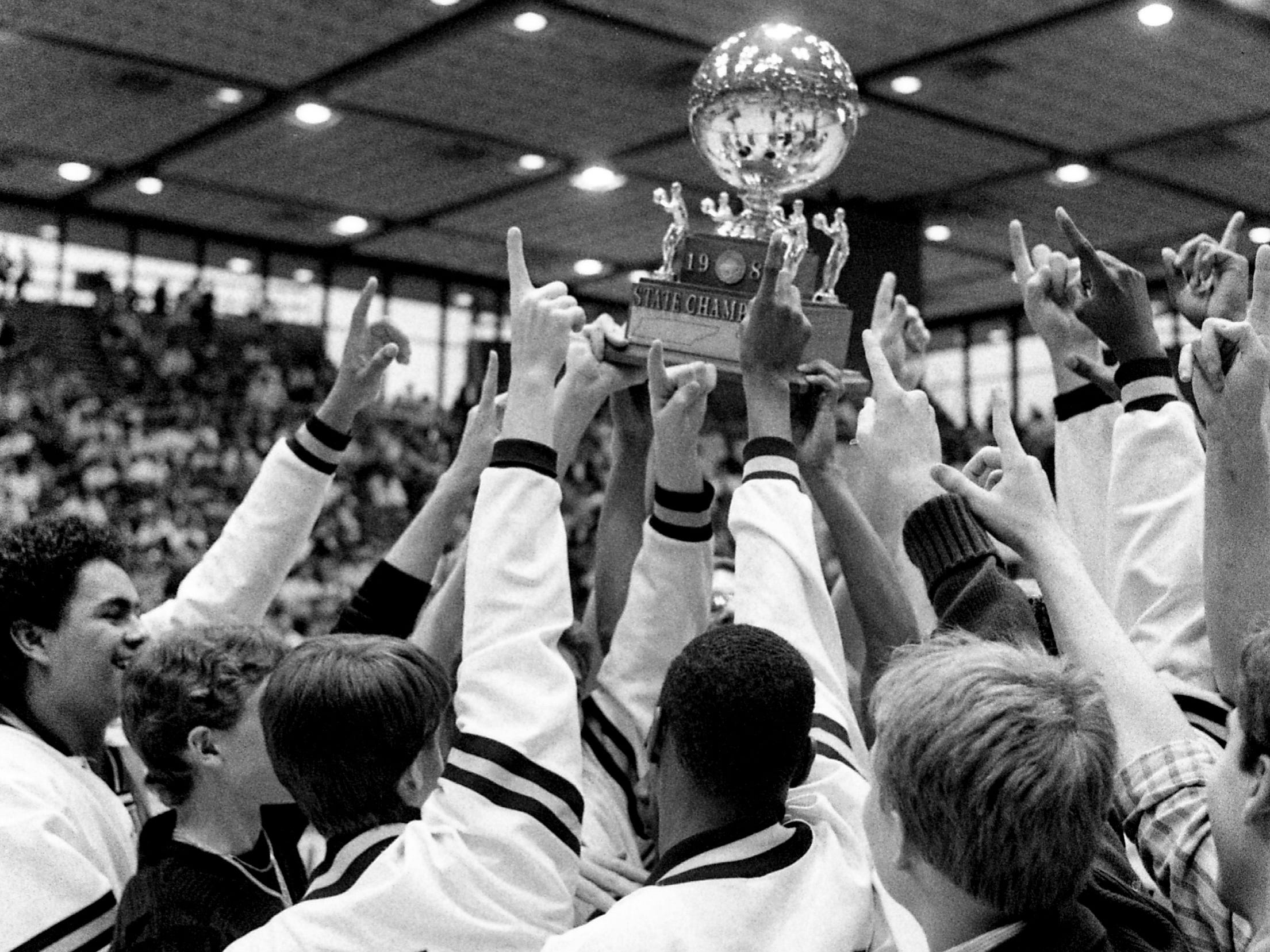 East Robertson High players celebrate after picking up the gold ball trophy for winning their unprecedented third straight Class A title at MTSU's Murphy Center in Murfreesboro on March 18, 1989.
