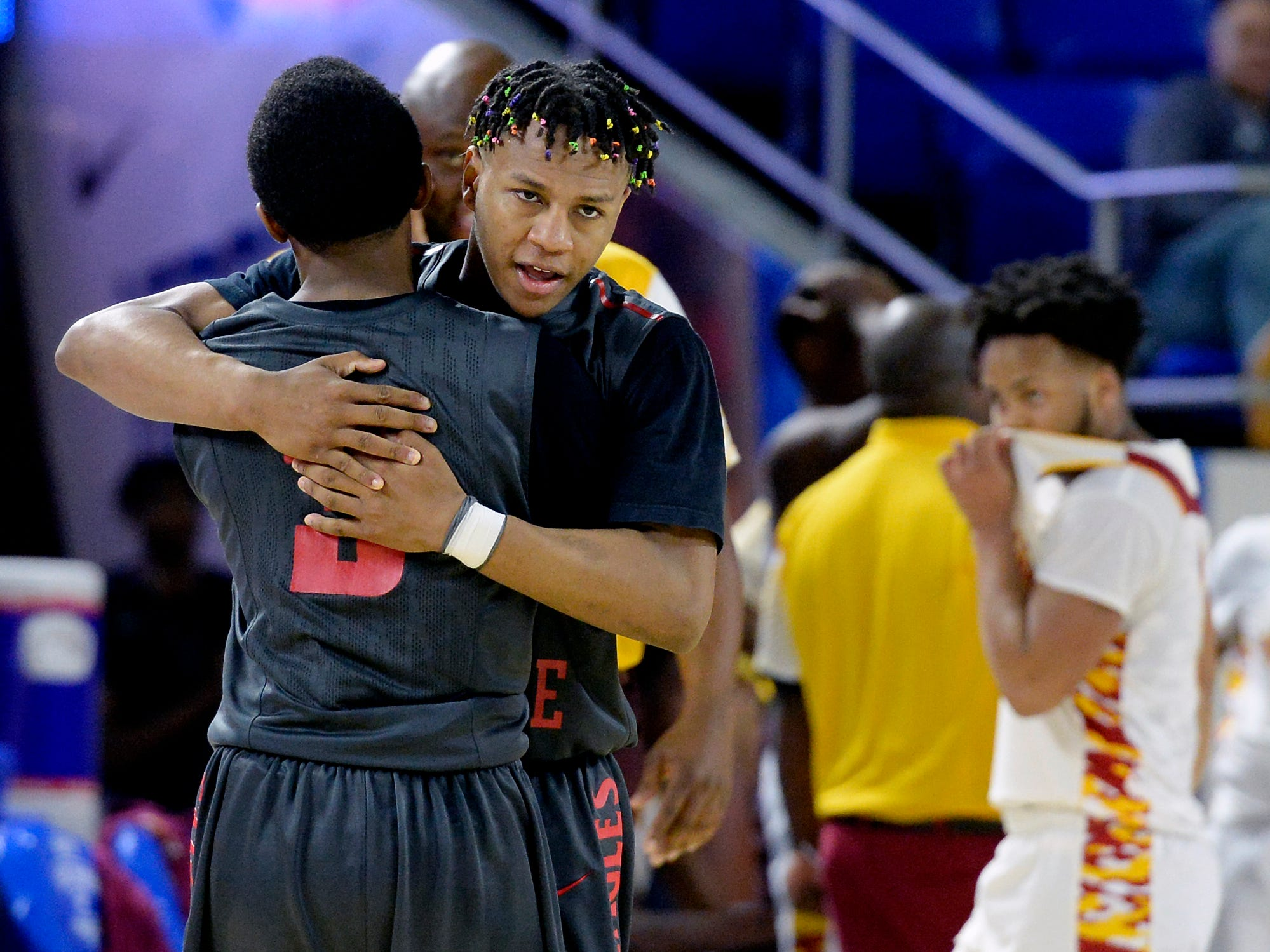 East Nashville guard Taras Carter hugs Caleb Grimes (3) after the team's 78-75 win against Howard in an Class AA boys' state basketball quarterfinal game Wednesday, March 13, 2019, in Murfreesboro, Tenn.