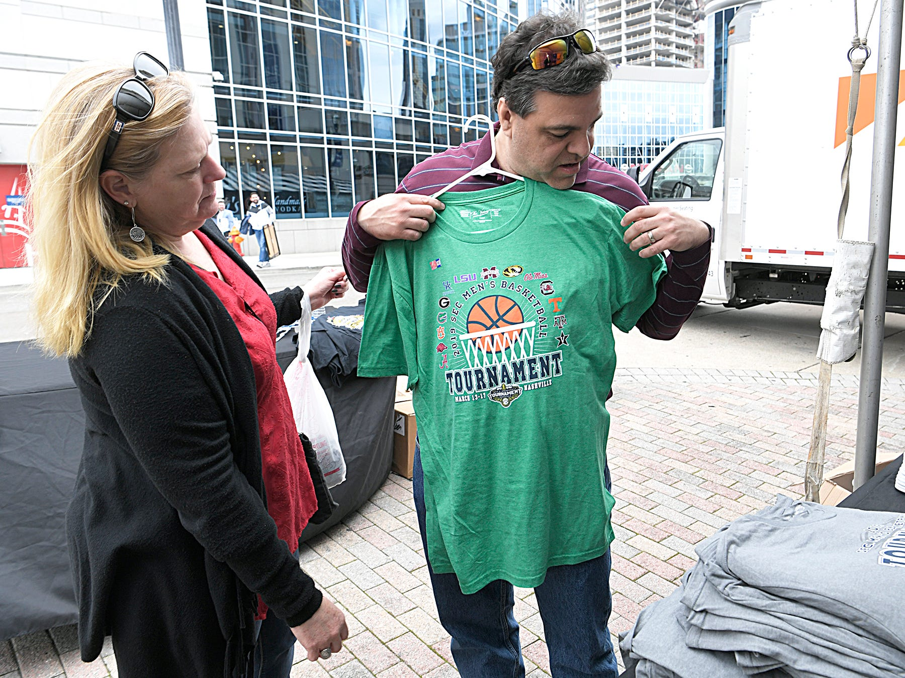 Lisa and Ed Alverez of Georgia purchase a SEC Men's Basketball Tournament T-shirt in downtown Nashville on Wednesday, March 13, 2019. The couple is not attending the tournament but they are Georgia fans.