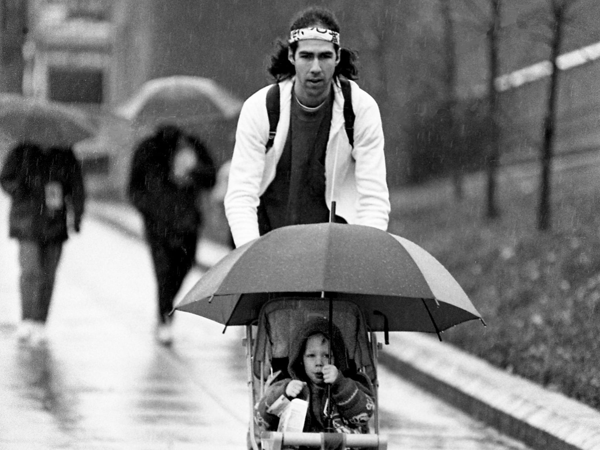Eric Talbot, 2½, keeps dry while dad Bryan keeps going during the AIDWALK Nashville that drew 150 participants March 18, 1989, despite the rainy, cool weather. Walkers, runners and a few folks in wheelchairs made the 6.2-mile trek from the Vanderbilt University's track through downtown Nashville and back to raise money for AIDS research.
