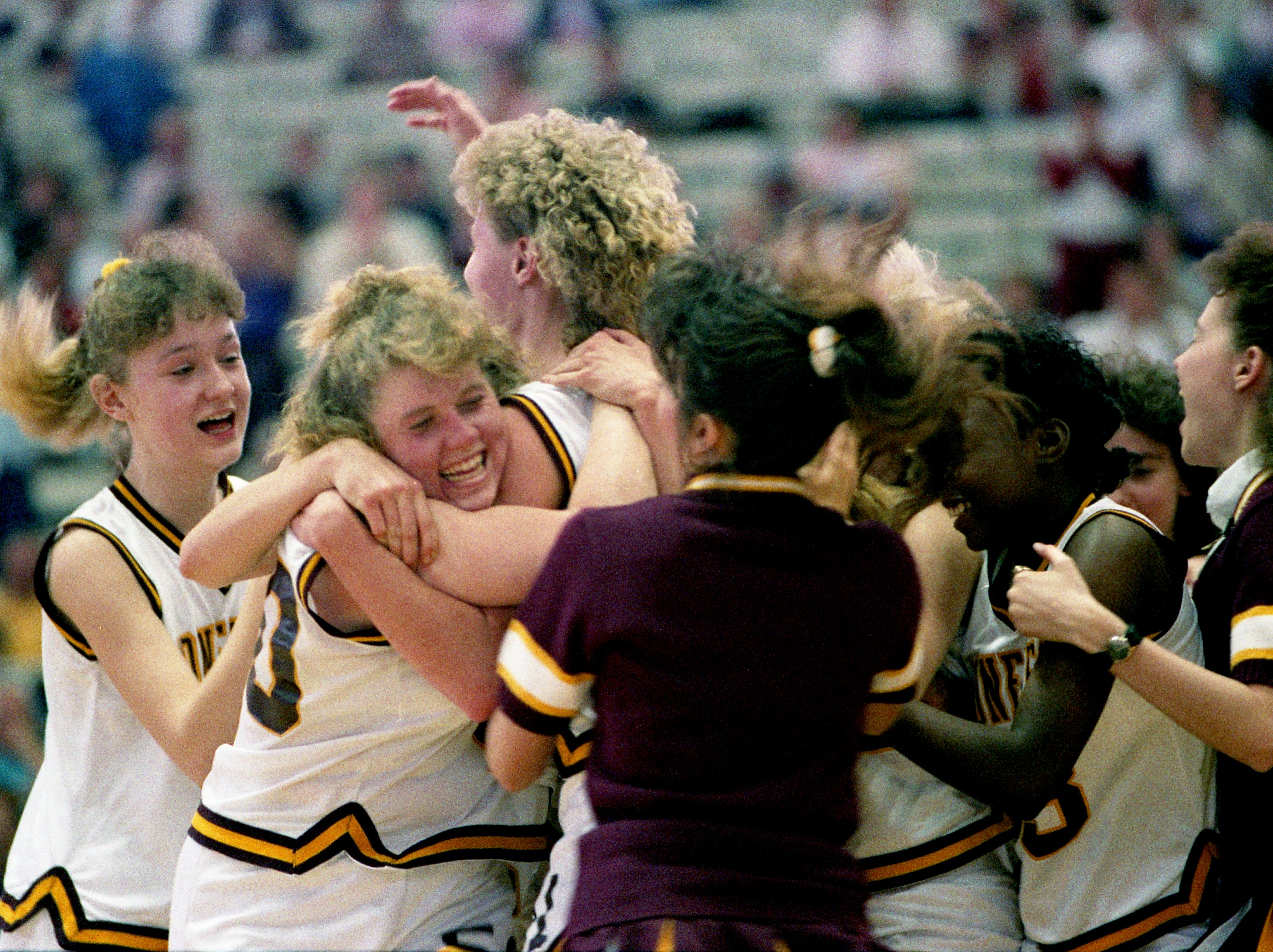 Jubilant Cannon County High players Tara Soloman, Reggie King, Julie Powell and others celebrate their 67-60 overtime victory over two-time defending champions South Greene during the first round of the TSSAA Class AA State tournament at MTSU's Murphy Center in Murfreesboro on March 9, 1989.