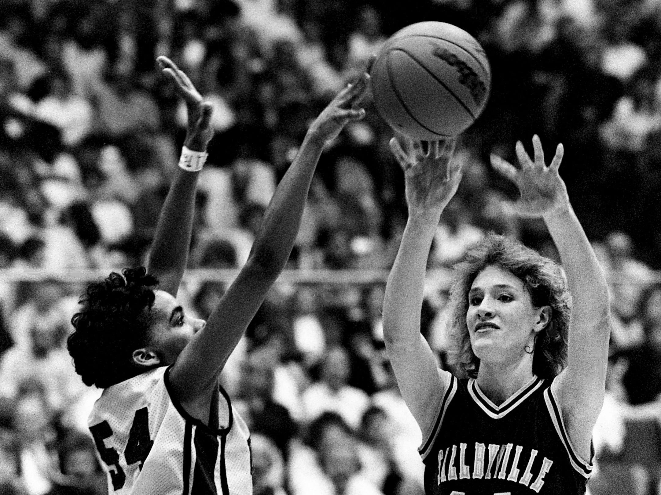 Shelbyville High junior Misty Lamb (14) passes over Oak Ridge High's Cynthia Dunnigan in the Golden Eaglettes' 55-47 victory over Oak Ridge to win the TSSAA Class AAA State Tournament title at MTSU's Murphy Center in Murfreesboro on March 11, 1989. The USA Today No. 1 nationally ranked Shelbyville finished with a 36-0 record and won their second state title in four years.
