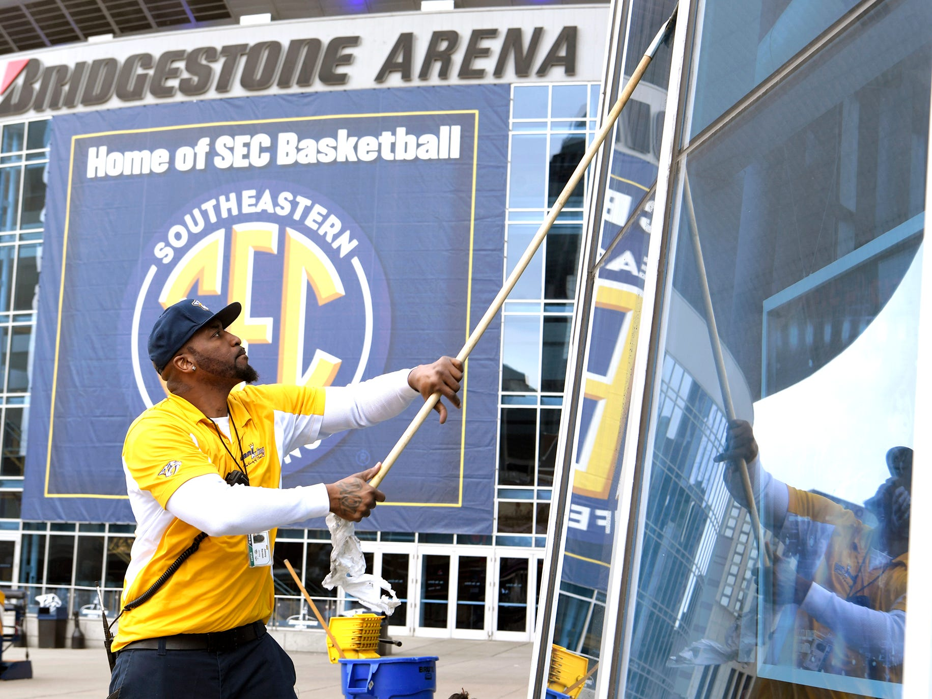 Johnny Harmon cleans the windows outside Bridgestone Arena before the SEC Men's Basketball Tournament in Nashville on Wednesday, March 13, 2019.