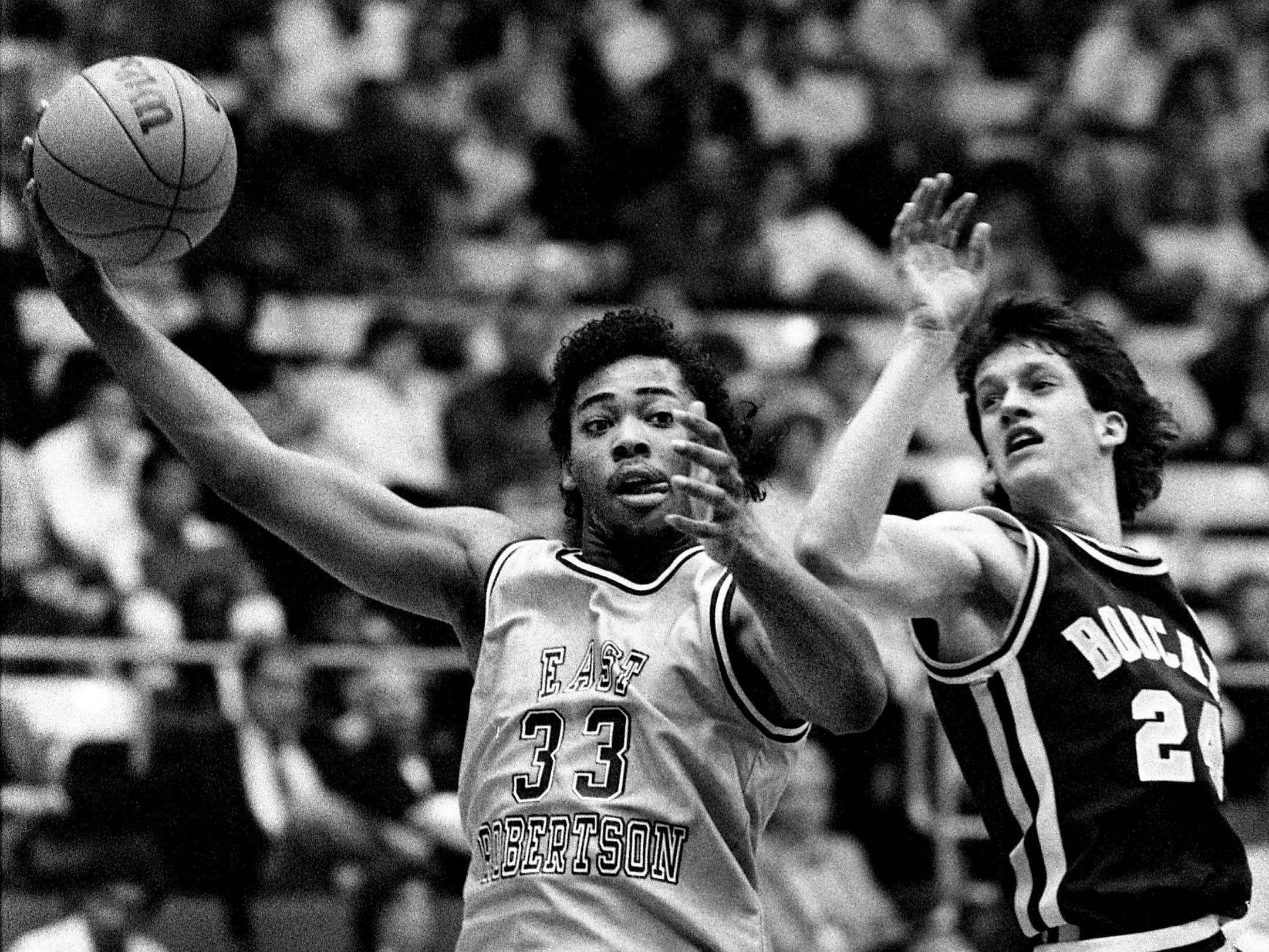 East Robertson High senior center Carlus Groves (33) makes his move inside past Oliver Springs High's Paul McDonald (24) for two of his game-high 36 points in their 83-62 win during the TSSAA Class A championship game at MTSU's Murphy Center in Murfreesboro  on March 18, 1989. Groves, Class A Mr. Basketball, hit 18 of 21 shots to go along with 17 rebounds.