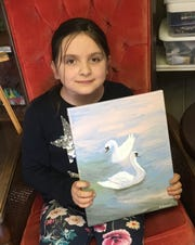 Anastasia Tamm, 8, shows off her favorite painting to date, a pair of swans.