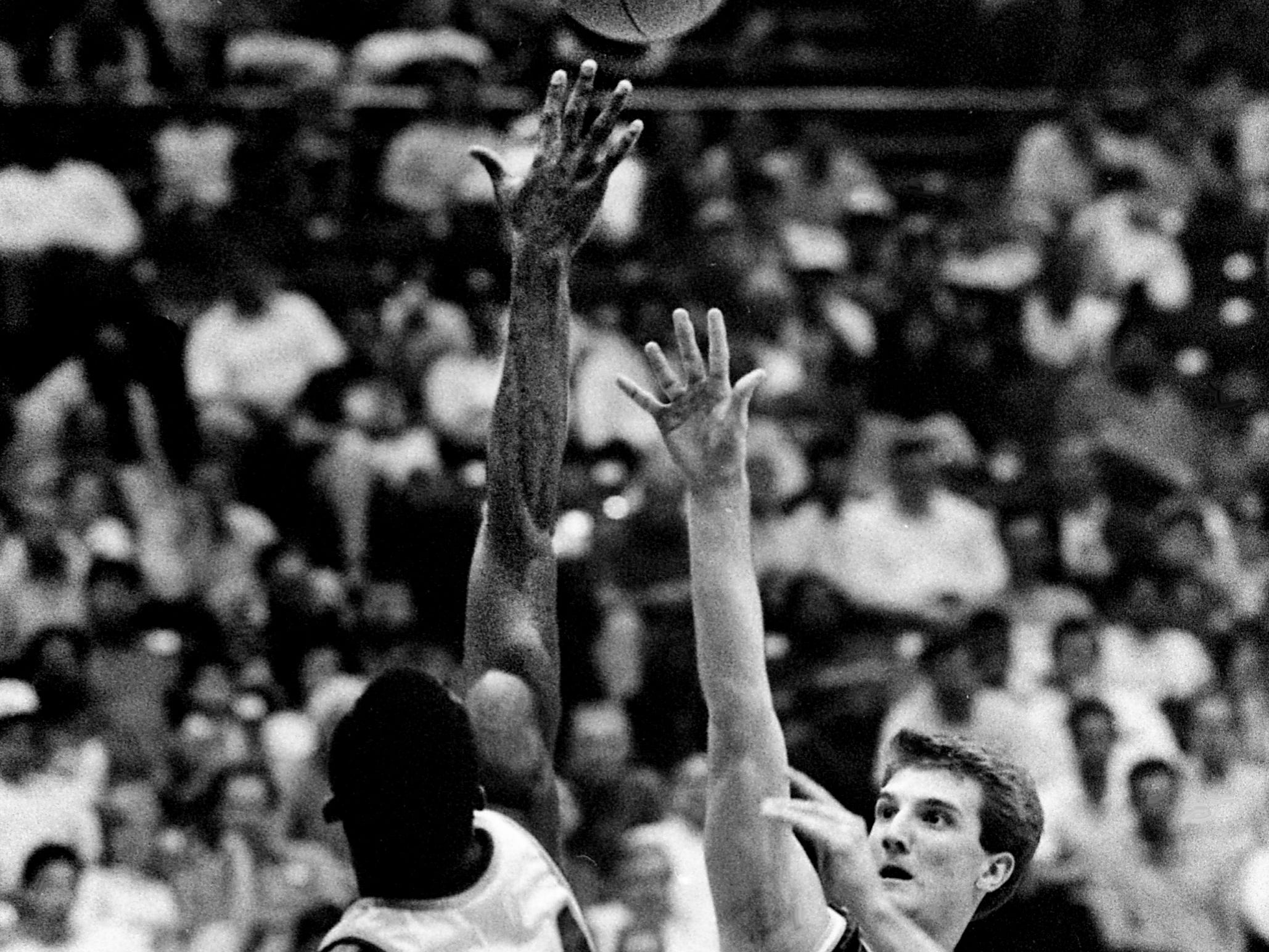 Franklin High senior guard Kevin Anglin (40) just gets his shot over the reach of Shelbyville High's Dewayne Fishback for two of his 19 points in Franklin's 53-51 victory the TSSAA Class AAA semifinal game at MTSU's Murphy Center in Murfreesboro March 17, 1989.