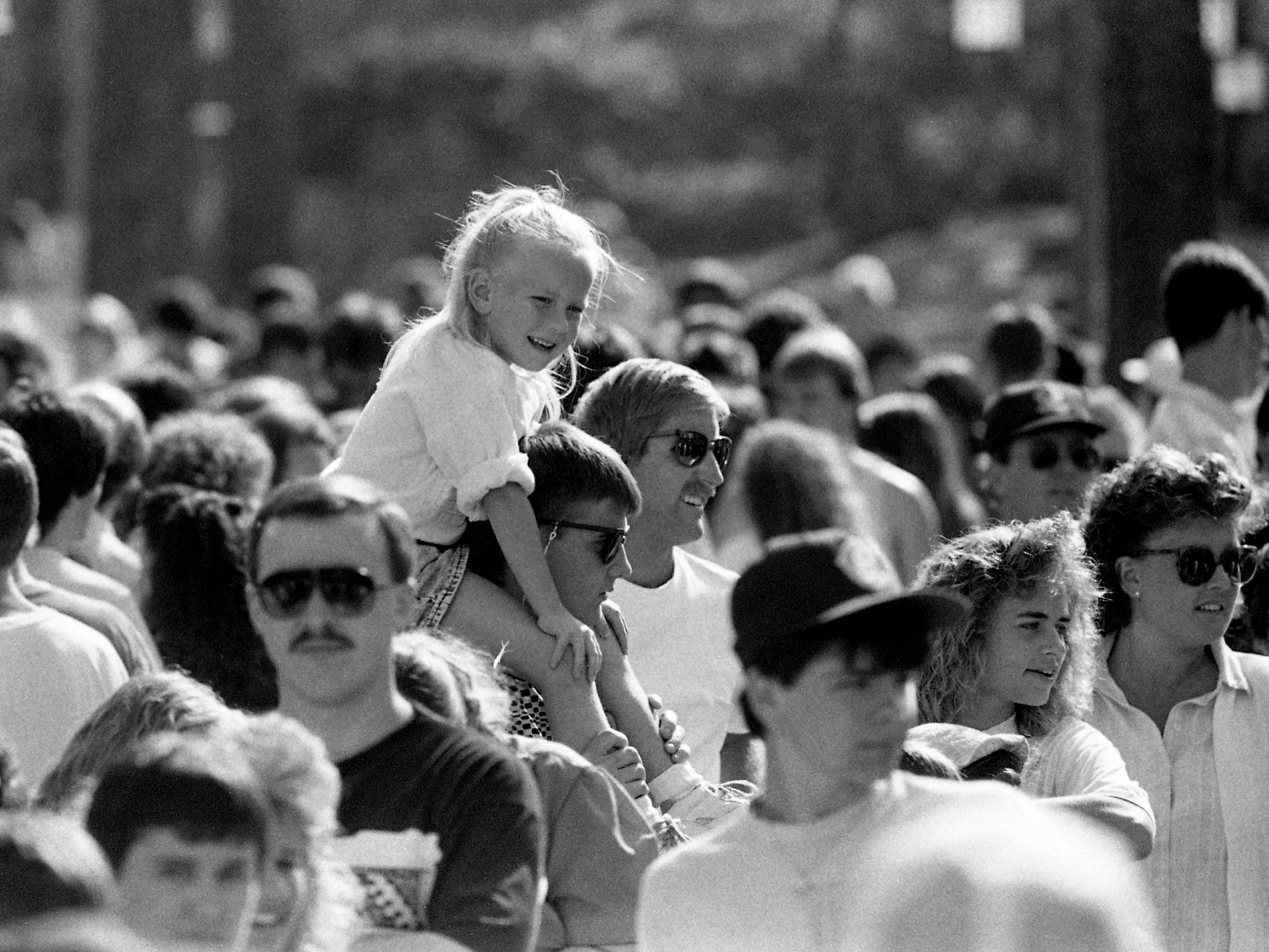 Californian Jody Inman gives his sister Tiffany a lift while they wait in line for the debut of Opryland U.S.A. theme park's new $7 million ride, Chaos, on opening day of the 18th season March 25, 1989.