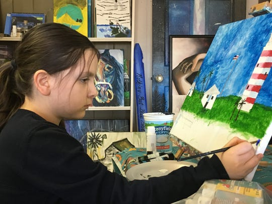 Anastasia Tamm works on her newest painting at the Studio 76 Artists Group in White House, Tenn.
