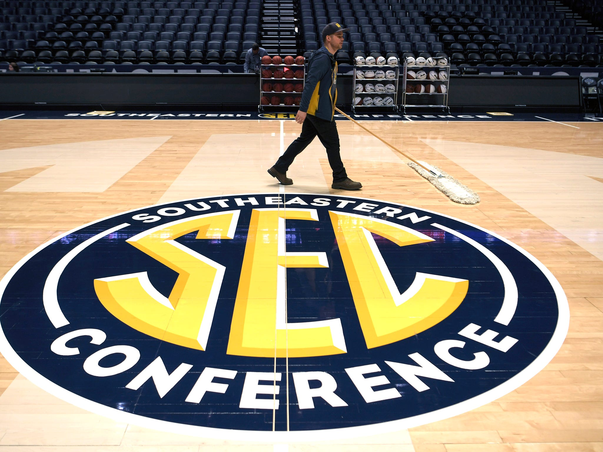 Patrick Hatton sweeps the basketball court before team practice at the 2019 SEC Men's Basketball Tournament in Nashville on Wednesday, March 13, 2019.