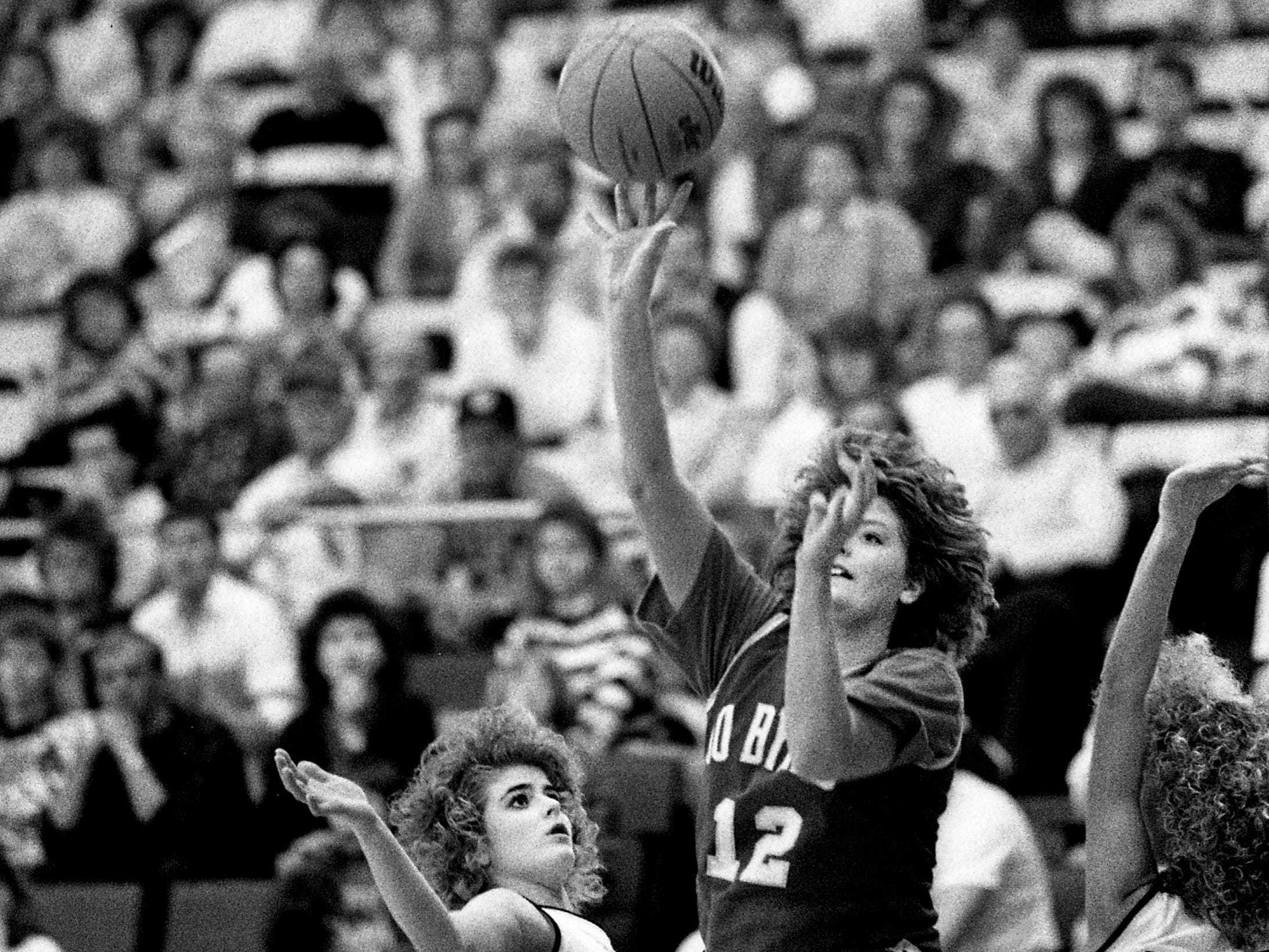 Mary Frank Fletcher (12) of Jo Byrns High scores two of her 11 points over defender Annette Aaron of Pickett County High. But it was enough as Pickett County won 62-60 in the opening game of the TSSAA Class A State tournament at MTSU's Murphy Center on March 8, 1989.