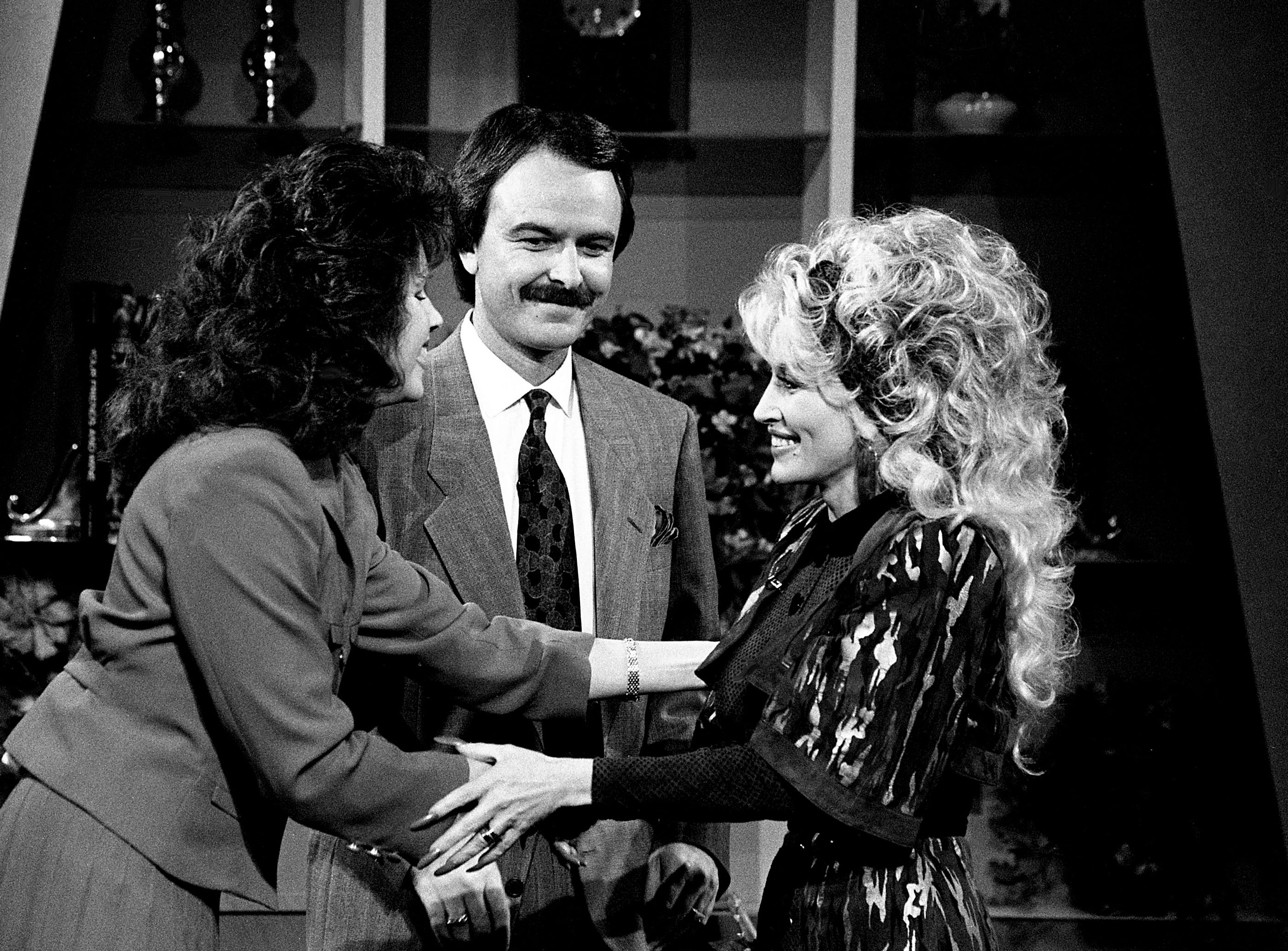 """Special guest Dolly Parton, right, is welcomes by Lorianne Crook, left, and Charlie Chase on the set of """"Crook and Chase"""" on March 24, 1989. Parton has been finishing work on her next album."""