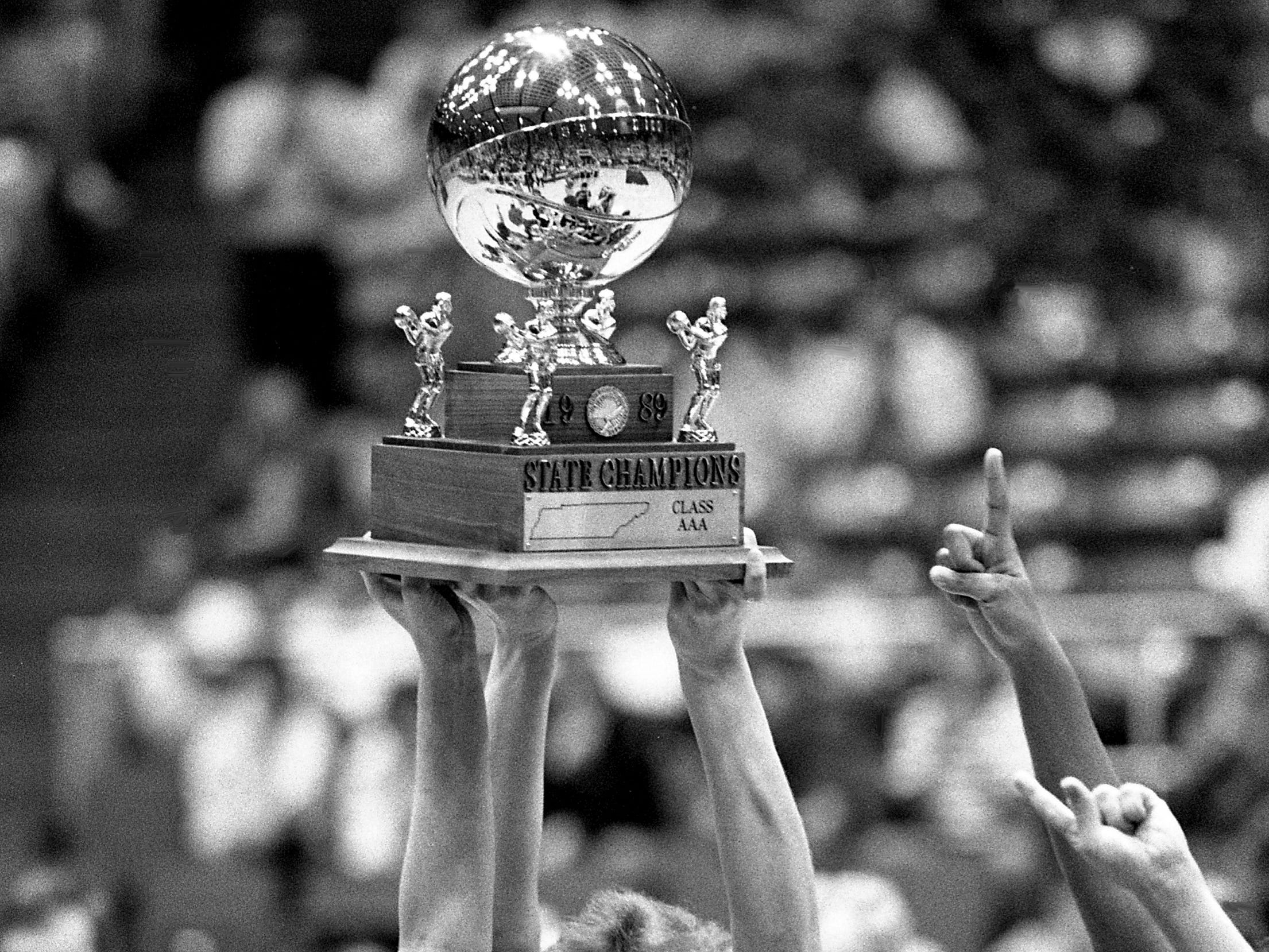 Tournament Most Valuable Player Misty Lamb (14) lifts Shelbyville High's Class AAA state championship trophy after their 55-47 victory over Oak Ridge at MTSU's Murphy Center in Murfreesboro on March 11, 1989. The USA Today No. 1 nationally ranked Shelbyville finished with a 36-0 record and won their second state title in four years.
