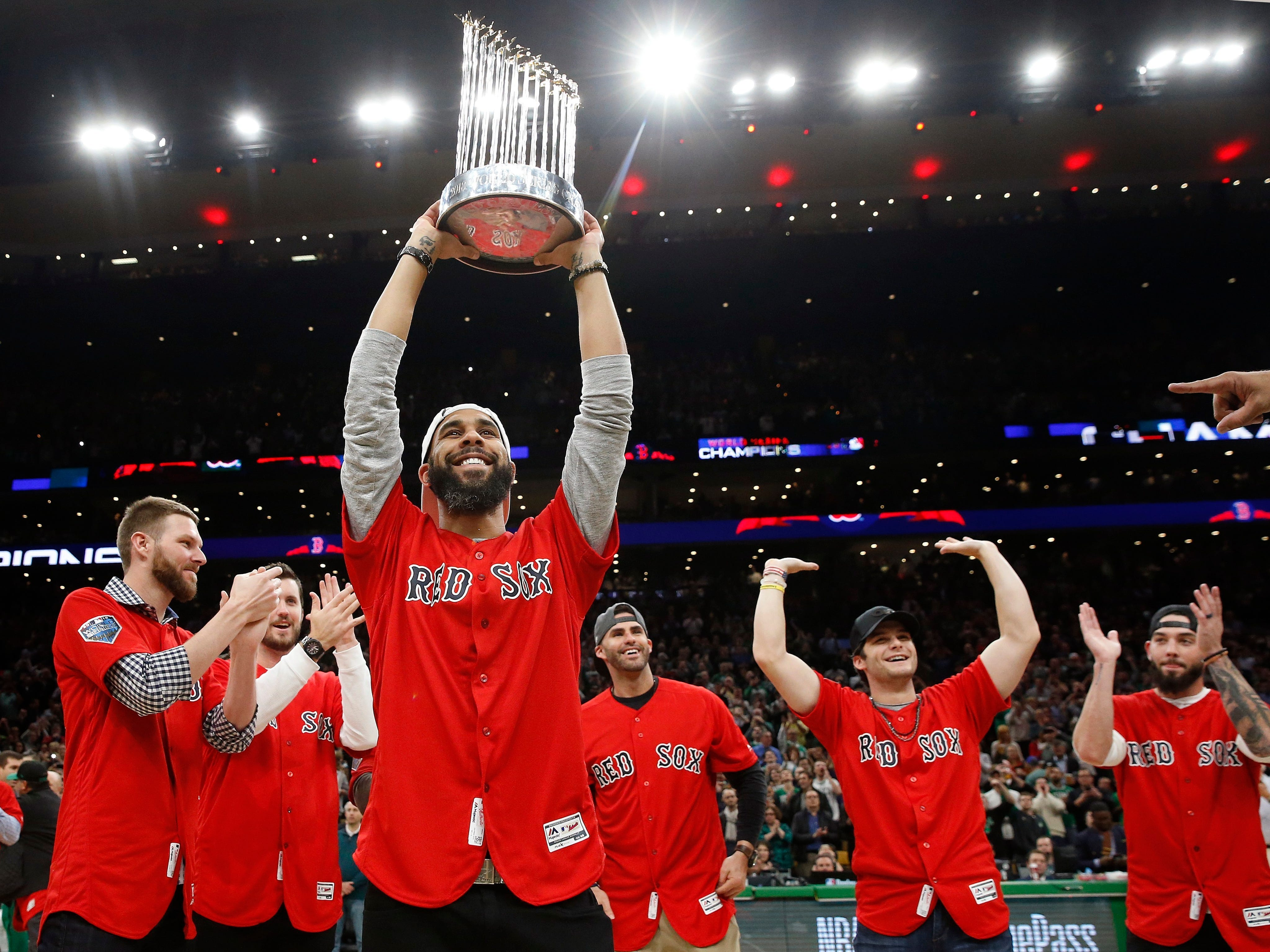 Boston Red Sox's David Price holds up the World Series trophy with teammates during the game between the Boston Celtics and the Milwaukee Bucks in Boston on Nov. 1, 2018.