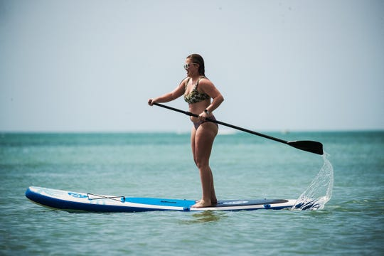 Macy Behm, 18, a resident of Tyler, Texas tries her hand at paddleboarding on Bonita Beach on Wednesday 3/13/2019. She is on spring break with her family.