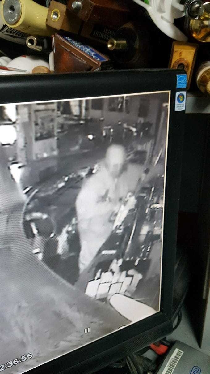 Surveillance footage of a suspect stealing cash and liquor from Crossroads Bar on National Road.